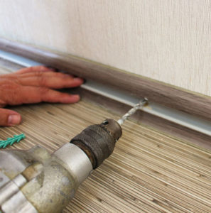 The man secures the baseboard to the wall